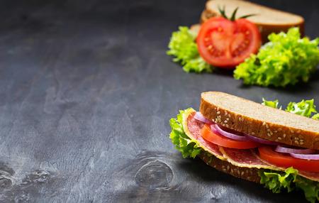 bocadillo: Sandwich con tomate, salami, ensalada, cebolla en el fondo oscuro. Enfoque selectivo. Copiar espacio de fondo