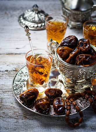 traditional celebrations: Traditional arabic tea and dry dates. Selective focus. Toned image