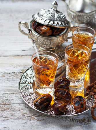 Traditional arabic tea and dry dates. Selective focus