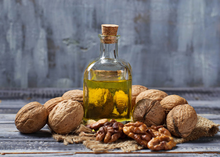 Walnut oil in bottle and nuts. Selective focus