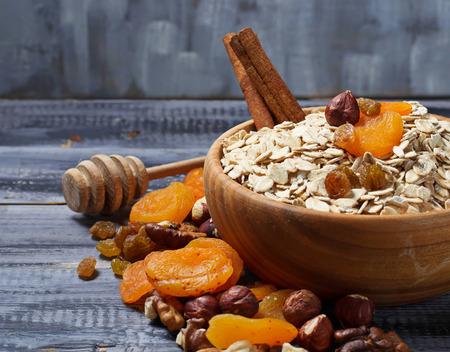 Ingrediënt voor muesli: havermout, honing, gedroogde vruchten, noten. selectieve aandacht