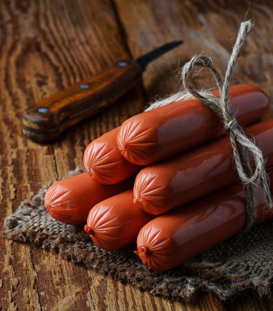 uncooked: Uncooked sausages on wooden background. Selective focus
