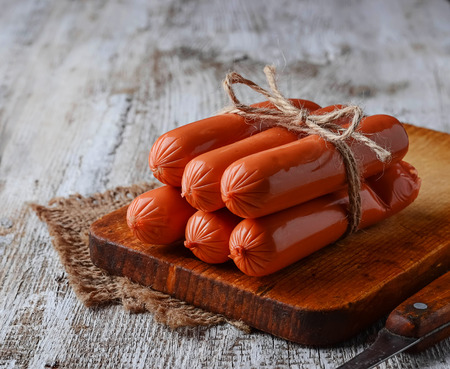 Uncooked sausages on wooden background. Selective focus