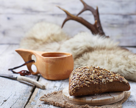 pelage: Rue bun with seeds and finnish cup kuksa. Selective focus