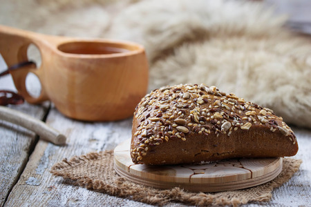 finnish: Rue bun with seeds and finnish cup kuksa. Selective focus