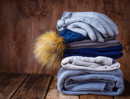 Stack of warm knitted clothes, sweaters and hat. Selective focus