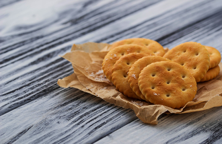 salty: Salty cracker and salt on wooden background. Selective focus
