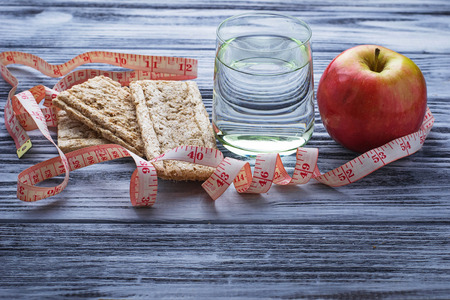 Concept of diet food: water, apple, crispbread and measuring tape. Selective focus