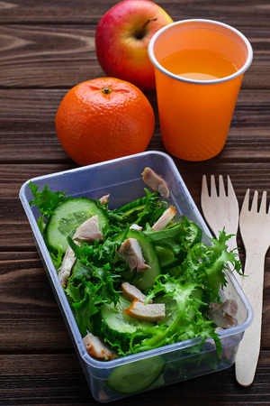 dinnertime: Lunch box with salad, apple, tangerine and juice. Selective focus