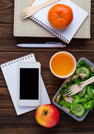 dinnertime: Lunch box with salad, notebook and phone. Selective focus, space for text