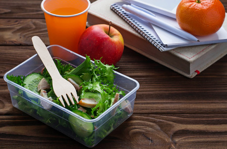 healthy snack: Lunch box with salad, apple, tangerine and juice. Selective focus, space for text
