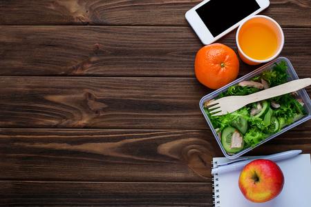 Lunch box met salade, laptop en telefoon. Selective focus, ruimte voor tekst