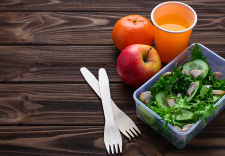 dinnertime: Lunch box with salad, apple, tangerine and juice. Selective focus, space for text