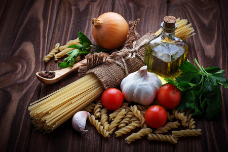 food backgrounds: Tomato, uncooked pasta, garlic, parsley. Selective focus