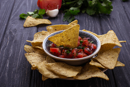 chips and salsa: Mexican corn chips nachos with salsa dip. Selective focus Stock Photo