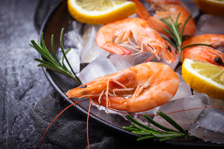 Prawns shrimps with lemon and rosemary. Selective focus Stock Photo
