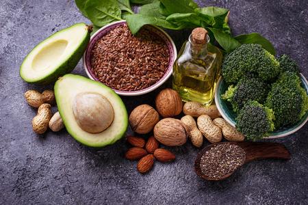 Veganistische vetbronnen - vlas, spinazie, broccoli, noten, olijfolie, olie en avocado. Concept van gezond voedsel