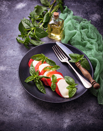 Italian caprese salad with mozzarella, tomatoes and basil. Selective focus