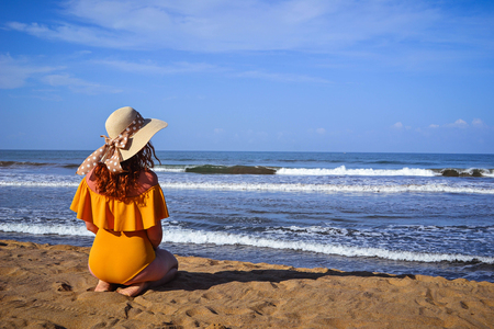 Red-haired girl in a yellow bathing suit and hat sits on the beach near the sea. Back view