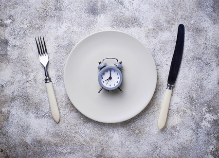 Grey alarm clock in empty plate. Stock Photo