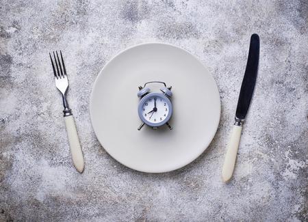 Grey alarm clock in empty plate. Archivio Fotografico