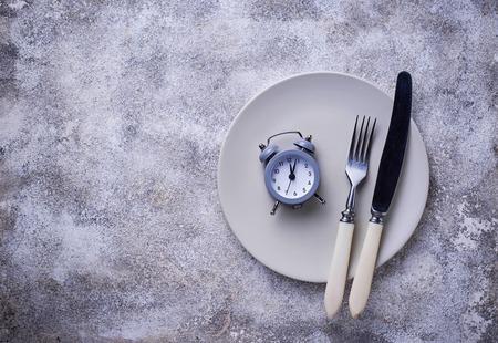 Grey alarm clock in empty plate. Stock Photo