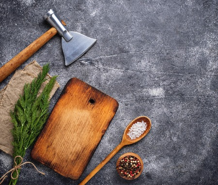 Culinary background with spices, cutting board and hatchet. Top view, copy space