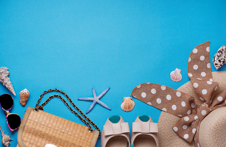 Summer beach accessories. Straw hat, bag, sunglasses and shoes on blue background
