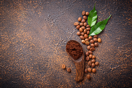 Roasted beans and ground coffee on rusty background. Top view