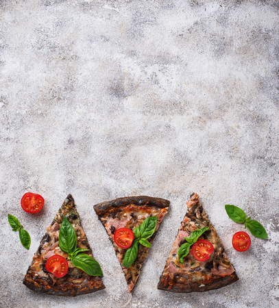 Pieces of  black pizza with tomatoes and basil. Top view Stock Photo