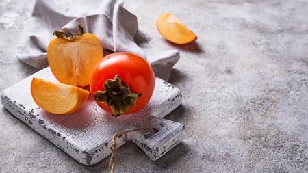 Fresh ripe persimmon on white cutting board