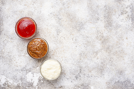 Set of different sauces: mustard, ketchup, mayonnaise on light background. Tio view