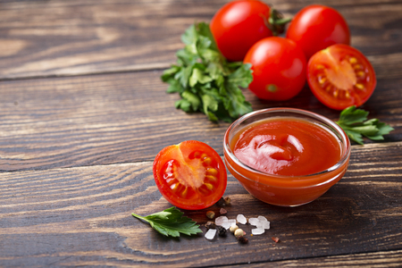 Tomato ketchup sauce on wooden background