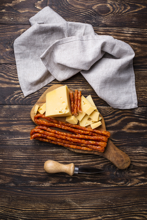 Cheese and salami sausage on wooden board