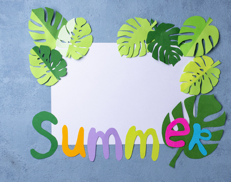 Summer background with monstera leaves from paper. Top view