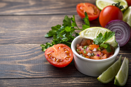 Traditional mexican tomato salsa sauce on wooden background Stock fotó