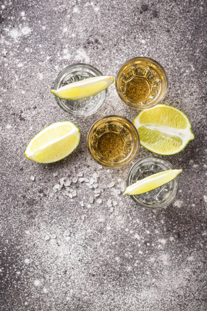 Shots of silver and gold tequila with lime and salt