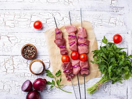 Raw shish kebab skewers or shashlik with tomatoes