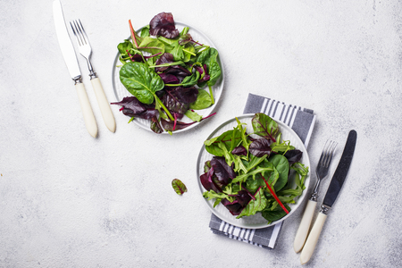 Mix of green salad leaves on light  background. Top view