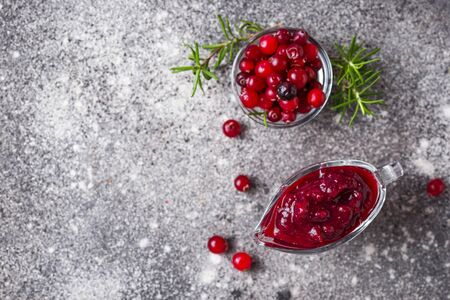 Cranberry sauce with rosemary and fresh berry on gray background