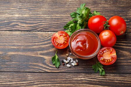 Tomato ketchup sauce on wooden brown  background