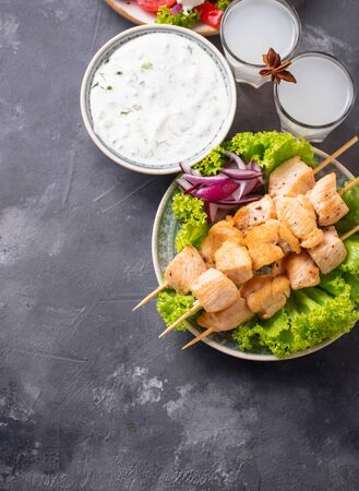 Tzatziki sauce, souvlaki and traditional greek dishes on grey background