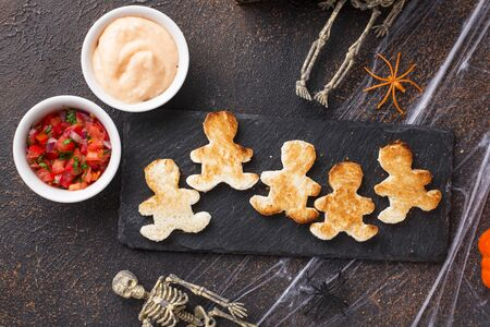 Bread in shape of men and sauces. Halloween scary appetizers.