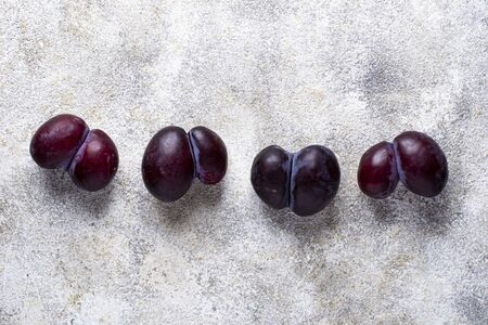 Ugly plums. Abnormal organic conjoined fruit in shape of heart or butterfly