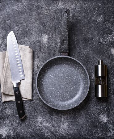 Empty grey stone frying pan on dark concrete background