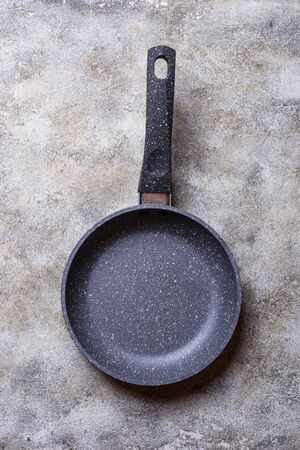 Empty grey stone frying pan on light concrete background