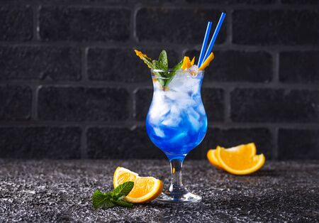 Blue cocktail drink with ice, mint and orange Foto de archivo