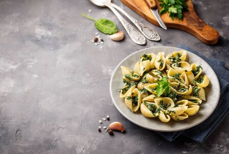 Conchiglioni pasta with spinach in creamy sauce