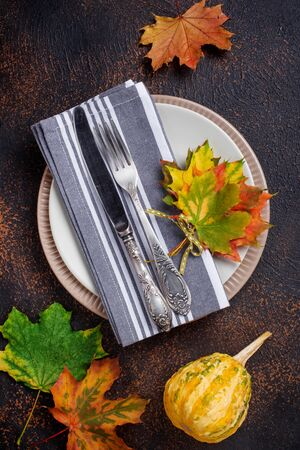 Autumn table setting with colorful leaves Фото со стока