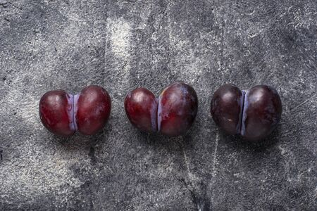 Oddly shaped plums. Abnormal organic fruit